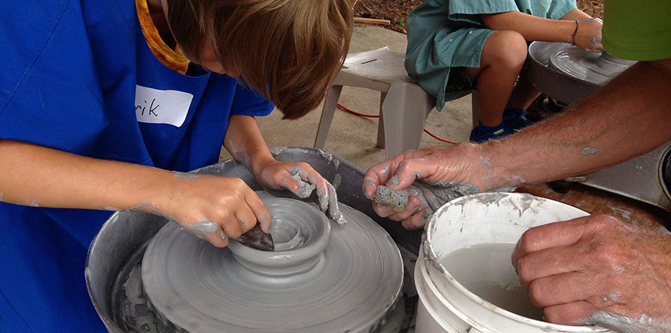 children making clay pots on a potter's wheel